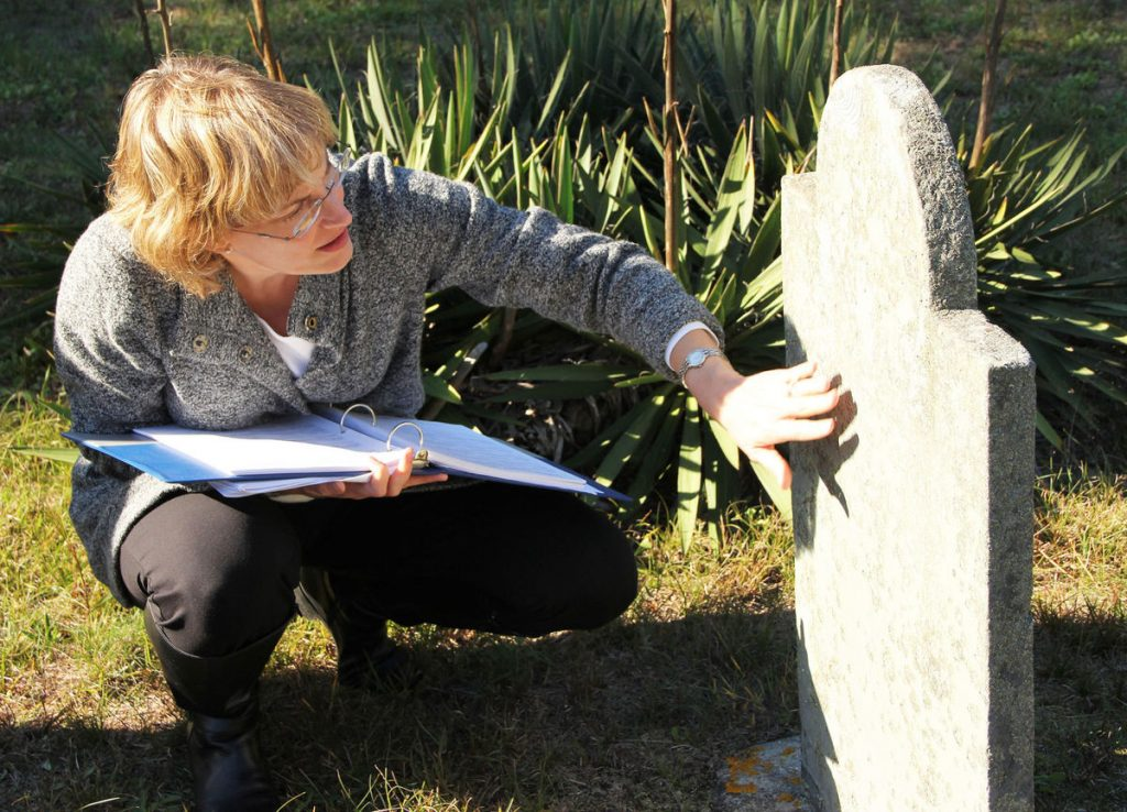 The Historical Commission's Jennifer Madden inspects a headstone at Cedarville Cemetery (CREDIT: Karen B Hunter -Enterprise
